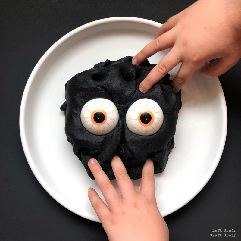 black playdough with monster eyes and hands playing in it