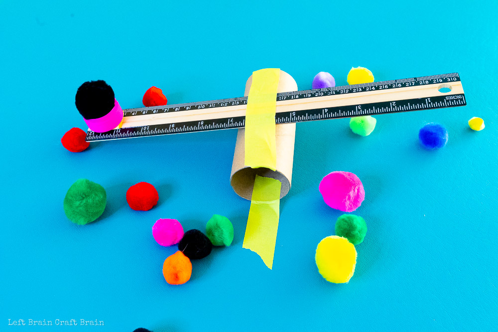finished toilet paper roll catapult with pom poms around it