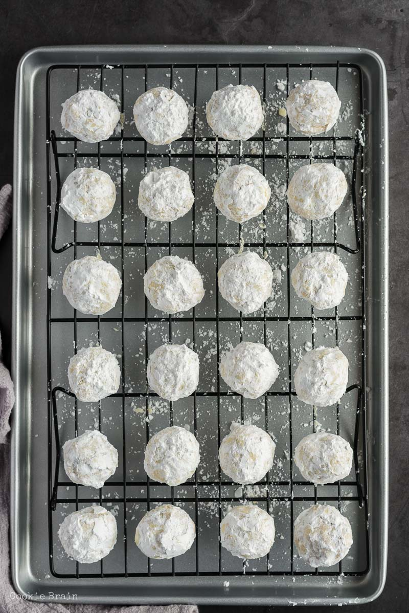 powdered sugar covered chocolate chip snowball cookies on baking rack
