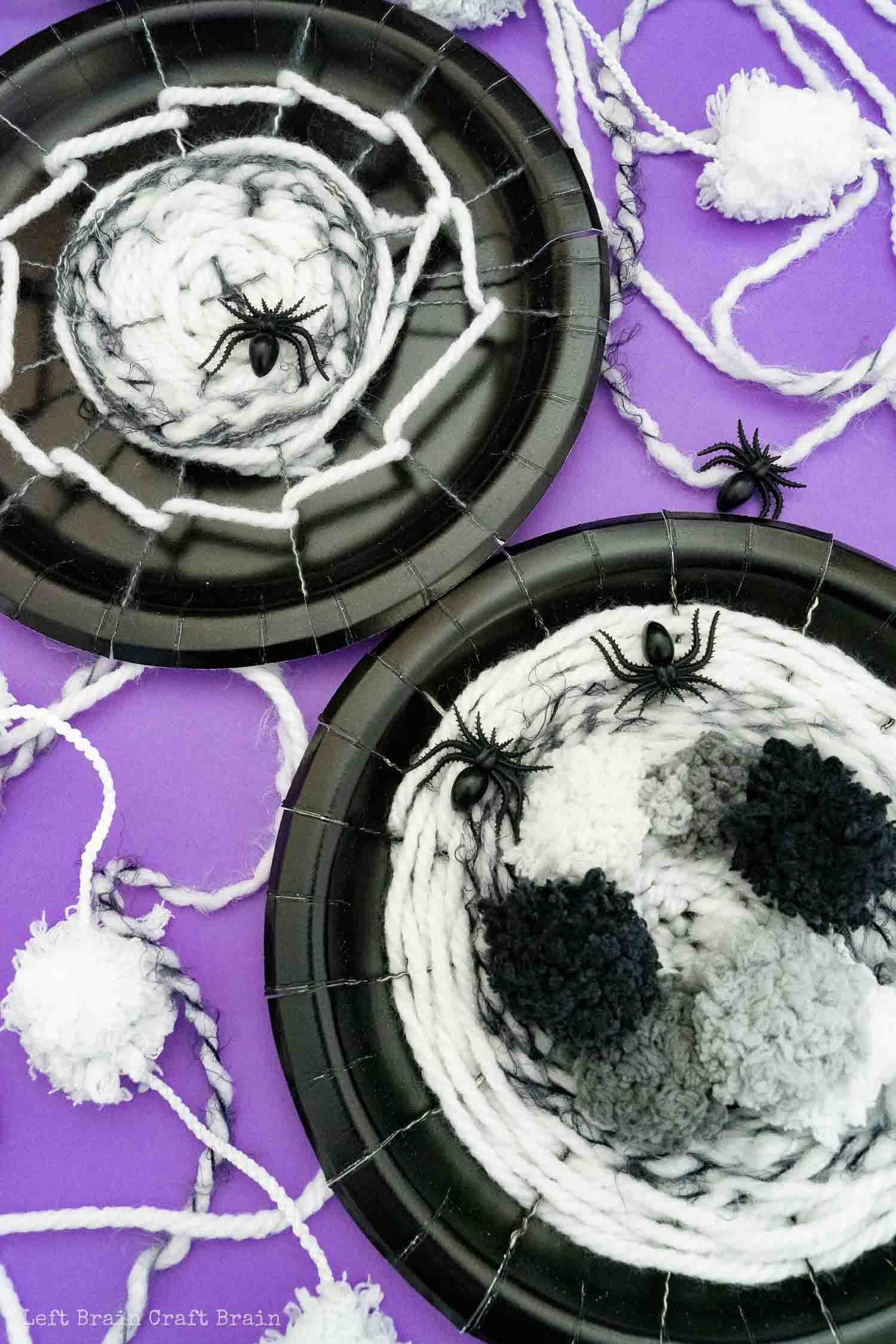 two different spider web weaving paper plates on purple with yarn and plastic spiders