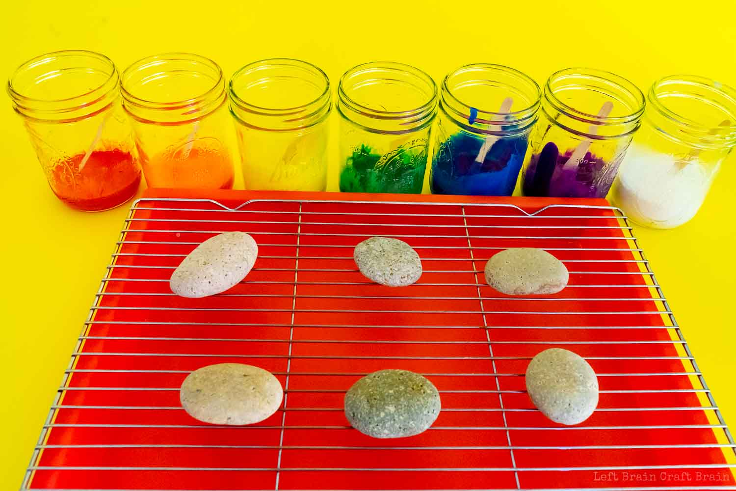 rocks on wire rack on tray in front of jars with different colors of paint in rainbow