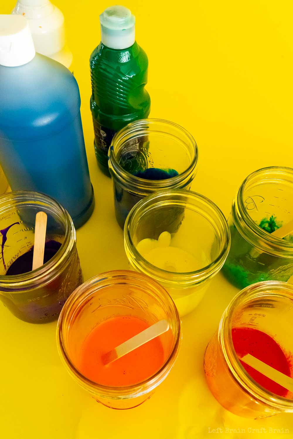 bottles of paint and jars of paint with popsicle sticks