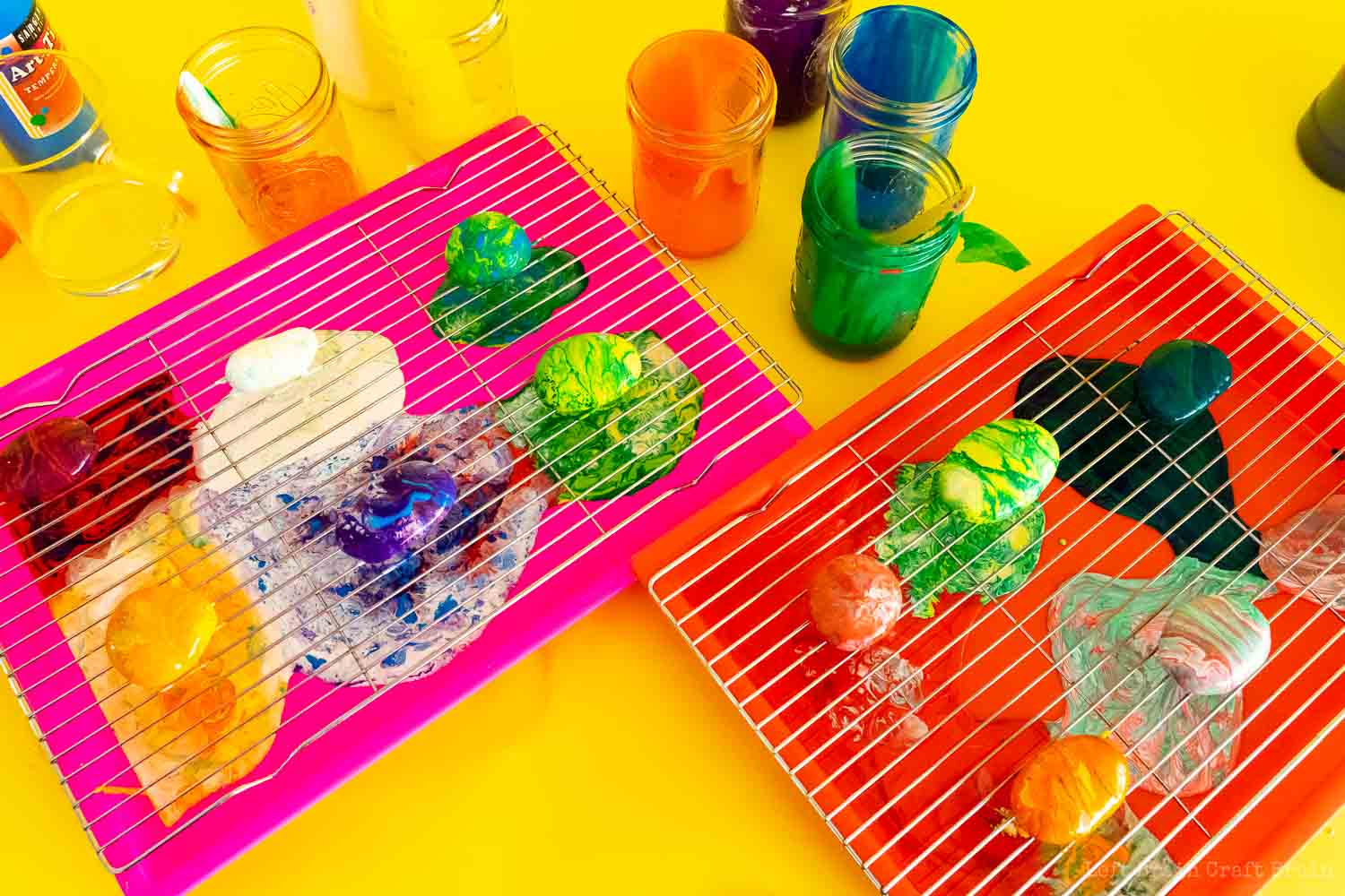 pour painted garden rocks on wire rocks on trays with jars of paint