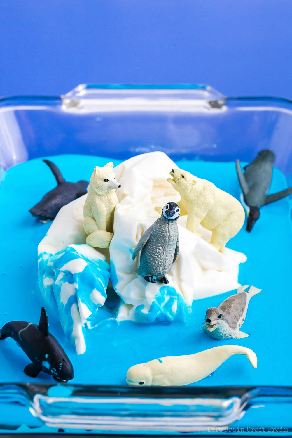 white frozen oobleck iceberg in pool of blue oobleck in glass tray with plastic polar animal toys like penguins orca seal polar bear