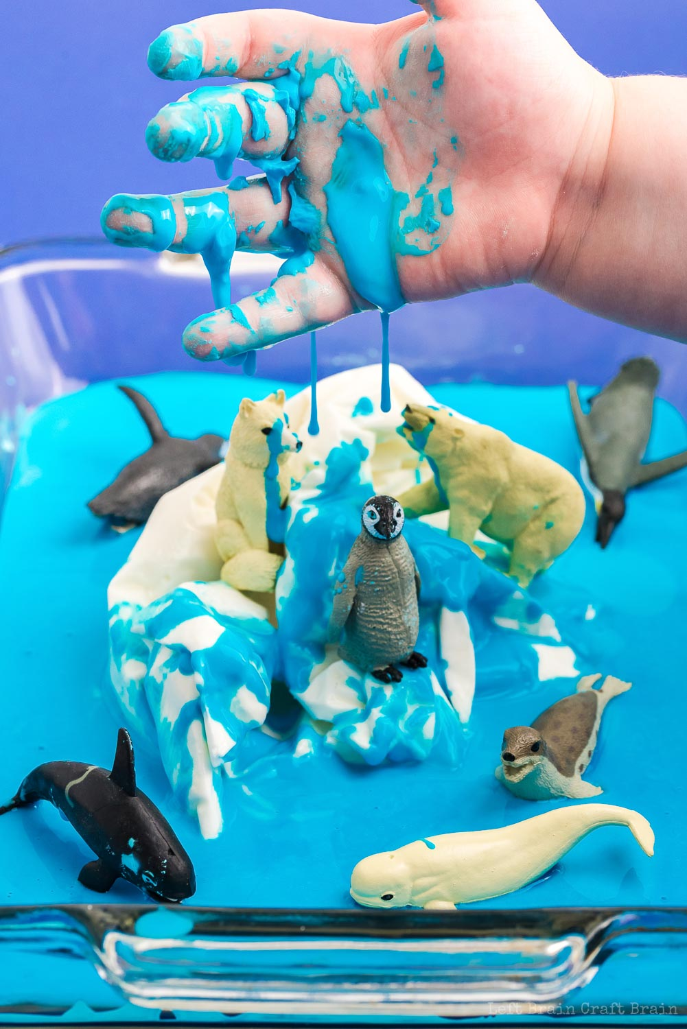 messy hand with blue oobleck over frozen oobleck iceberg with polar animal toys