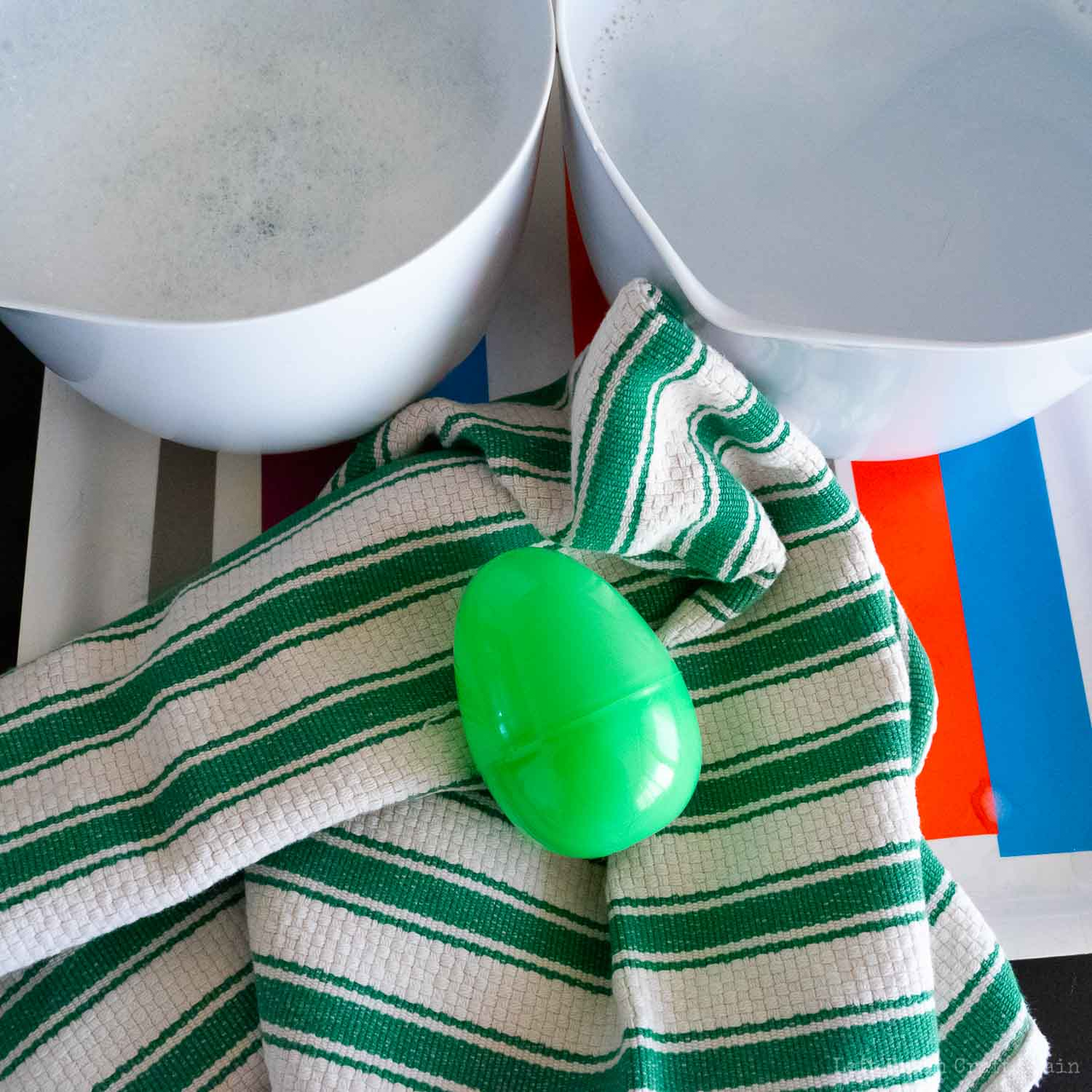 shake wool roving ball in easter egg inside of kitchen towel until a lot of the water comes out